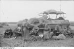 German troops resting beside a camouflaged SdKfz. 251/3 halftrack vehicle, Russia, Sep 1941