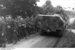 A camouflaged SdKfz. 251 halftrack vehicle passing a column of German troops, France, Jun 1944