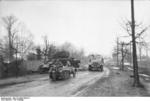 SdKfz 2 Kettenkrad and SdKfz 10 vehicles on a road in the Soviet Union, early 1944; note destroyed Sherman tank on the side of the road
