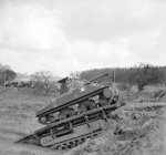 Sherman tank of UK 79th (Experimental) Armored Division Royal Engineers using a Churchill Ark armored ramp carrier to climb a small escarpment, 13 Feb 1944
