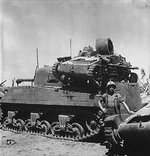 US Marine Private First Class N. E. Carling posing beside M4 Sherman tank