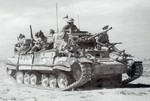 Valentine infantry tank of UK 23rd Armoured Brigade carrying Scottish troops of the UK 51st Highland Division in North Africa, circa mid to late-1942