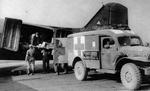 A patient being passed between C-47 Skytrain aircraft and Dodge WC54 ambulance, 1944-1945