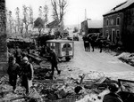 Jeeps, Dodge WC54 3/4-ton field ambulances, and US troops on a street in the heavily damaged town of Foy, Belgium, 16 Jan 1945