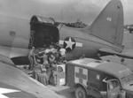 A Marine on Saipan was transferred to an R5C-1 Commando aircraft from a Dodge WC54 3/4-ton field ambulance for transfer to Hawaii, 1944; note the Jeep in between
