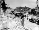 US Army convoy passing through the remains of Saint-Lô, France during the Normandy invasion, 29 Jul 1944; note Jeeps, CCKW 2-1/2 ton transports, Studebaker M29 Weasel, and Dodge WC54 field ambulance
