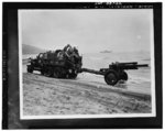 US Army two-and-a-half ton prime mover towing a 105 mm Howitzer M2 on the Algerian beach, North Africa, 1943