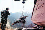 American helicopter lowering M101 105mm howitzer during the construction of a mountin-top fire base in Vietnam, 1 Jun 1968; the Marine in foreground was with US 3rd Marine Division