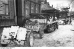 German Army SdKfz. 10 halftrack vehicle towing a 7.5 cm le.IG 18 field gun through a Russian village, Oct 1941