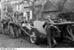 German troops moving a 7.5 cm PaK 40 anti-tank gun across a muddy road in Northern France, Oct 1943; note Kar98k rifles