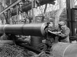 Female worker being helped out of a BL 15 in gun after she had finished cleaning the rifling, Coventry Ordnance Works, England, United Kingdom, 1914-1918