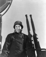 Bob Feller posing before a 40mm Bofors quad mount aboard a ship, possibly USS Alabama, 3 May 1943