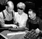 Chinese technicians speaking to a female Canadian Bren gun factory worker, 1940s