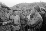 A Soviet soldier teaching partisan fighters how to operate a Browning Hi-Power handgun, near Smolensk, Russia, 23 Aug 1941