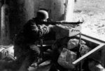 A German paratrooper defending a position with his FG 42 machine gun, Italy, circa 1944; note MP 40 submachine gun nearby