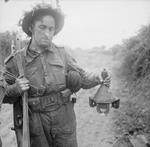 Lance Corporal Lodge of 278th Field Company, British Royal Engineers holding a captured German 3 HL shaped charge, near Caen, France, 26 Jun 1944