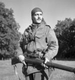 Canadian Calgary Highlanders Sniping Platoon Sergeant Harold A. Marshall posing with his Lee-Enfield No. 4 Mk. I rifle, Kapellen, Belgium, 6 Oct 1944