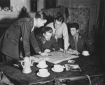 Allied Operation Jedburgh personnel receiving instructions from a briefing officer, London, England, United Kingdom, circa 1944; note M1 Carbine on table