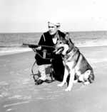 United States Coast Guardsman with M50 Reising submachine gun and dog on a beach in the United States, circa 1941-1945