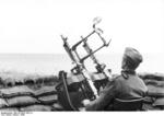German soldier on the French coast with a twin MG34 machine gun anti-aircraft mount, 1943