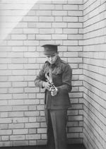 Australian Army Private Evelyn Owen posing with his invention Owen submachine gun, circa 1942