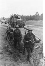 German Großdeutschland Division troops on a road at Memel, East Prussia, Germany, Oct 1944; note Panzerfäuste, Kar98k rifles, and grenades