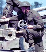 British soldier with Sten gun on a Soviet-built F-22 USV gun which had recently been captured from German troops, France, 1944
