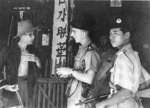 British-Malayan policemen talking to a civilian, Malaya, 23 Apr 1949; note Sten gun