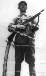 Chinese soldier standing guard with a Thompson submachine gun, date unknown